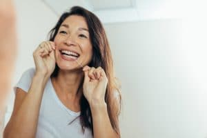 Woman looking in the mirror and smiling while she flosses her teeth.