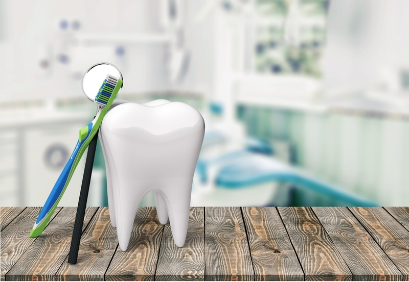 Dental office with a mirror, toothbrush and tooth leaning on a table.