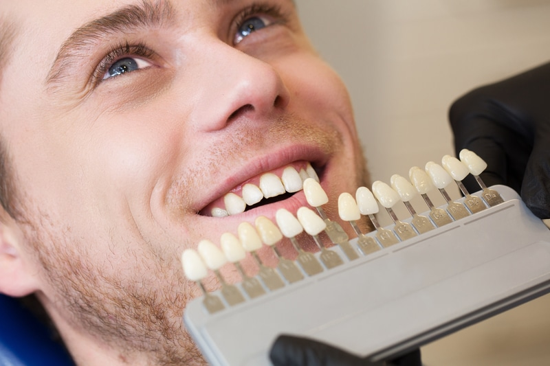 Close up of young man in dental chair selecting color of teeth he wants.