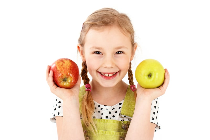 Cute little girl smiling and holding two apples in her hands