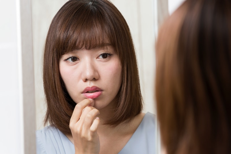 Young woman looking into the mirror and holding her lip with a sad expression on her face.