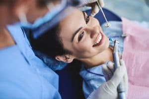 Woman sitting in dental chair smiling while receiving dental cleaning.