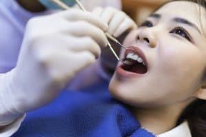 Woman having a dental exam and cleaning performed.