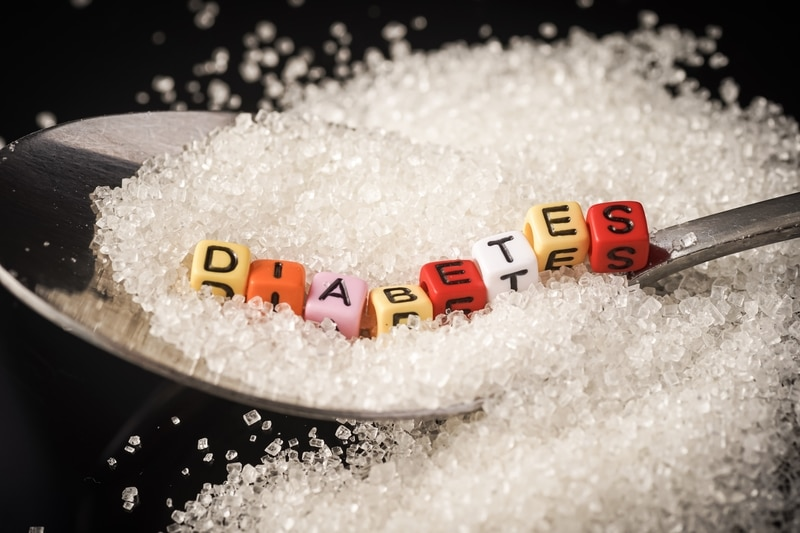 "Beads that spell out the word ""diabetes"" sitting on a pile of sugar and a spoon."