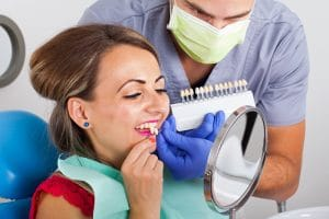 Female dental patient deciding which shade of veneer to be placed in her mouth with the help of the dentist by her side.