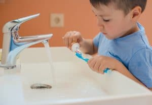 Young boy putting toothpaste on his toothbrush to brush his teeth.