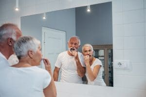 An older man and woman brushing their tooth together in front of the bathroom mirror.