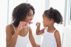African American mother with her young daughter brushing their teeth
