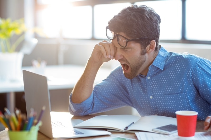 Male business executive yawning in front of his computer