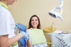 Young woman sitting in dental chair shaking hand with dentist.